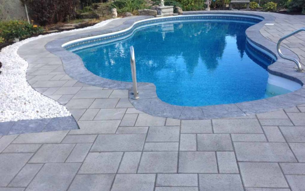 aménagement paysager cour arrière avec contour de piscine en pavé uni